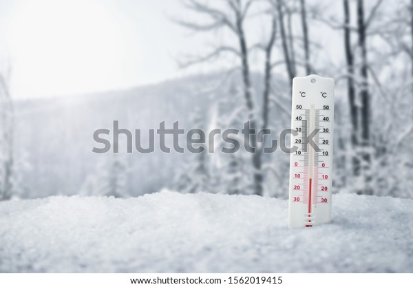 Thermometer in snow, winter, snowing background