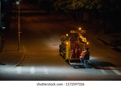 Thermoplastic spray marking machine during road construction works at night. Traffic line painting on asphalt