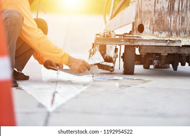 Thermoplastic spray marking machine during road construction. Workers painted white lines on the road surface. (Road Workers Paint) Thailand Asia