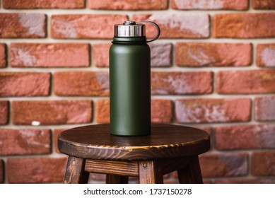 Thermos bottle near brick wall background. Coffee or tea reusable bottle container. Thermos travel tumbler. Insulated drink container.