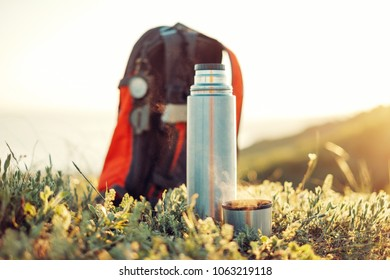 Thermos and cup of hot drink near the backpack outdoor in summer.