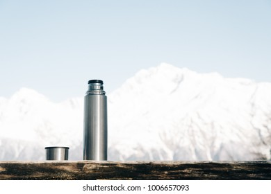 Thermos with cup on a wooden table on background of snowy mountains in winter.