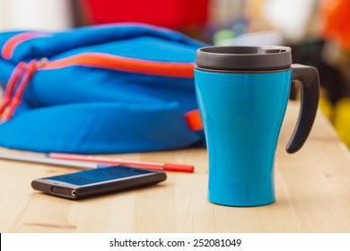 Thermos cup, smart phone and sports bag on wooden table. A healthy lifestyle concept.