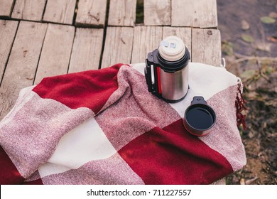 Thermos with a cup standing on a plaid on a wooden bridge near lake. Autumn mood