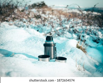 Thermos flask with two cups on the snow in winter, concept of drinking hot liquid during a hike