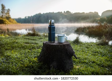 Thermos mug with hot drink on the background of the lake. Steam comes from the mug. A blue vacuum theroms stands on a tree stump in the wild.