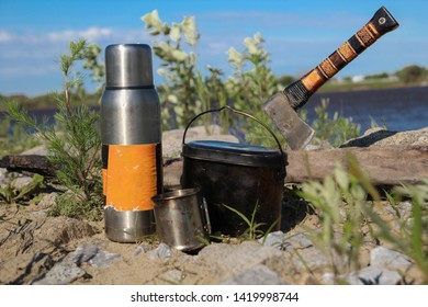 Thermos, pot, mug, hatchet stuck in a wooden log - a set of hiking tourist for camping and trekking in the woods and nature