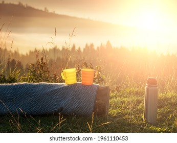 Thermos and two bright cups on a log overlooking the mountain landscape in the early morning at sunrise. The atmosphere of travel and outdoor recreation.