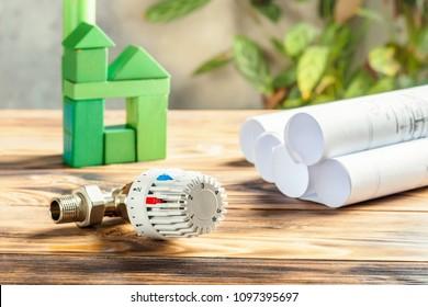 Thermostatisches Heizventil für Heizkörper und grünes Haus von Würfeln auf Holzhintergrund Heizprojekt Wärmeversorgung Gebäude Konzept für ökologische Nachhaltigkeit und Energieeinsparung.