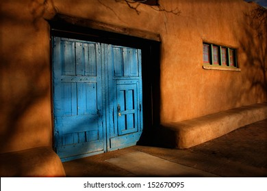 These heavy, bright blue wooden doors, are offset by the rich, warm tones of sunrise on the Adobe walls of this Santa Fe, New Mexico structure. Strong lighting and shadows adds mystery to this scene.