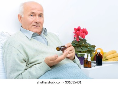 These are medicines. Elderly man sits on his bed and holds pills vial while there are other remedies on the background.