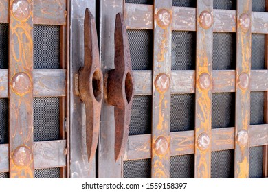 These pick axes steel heads are used as handles to open this rusty looking door with a checkered pattern.  A pick ax is used to dig lose dirt.  These were re-purposed as door handles.