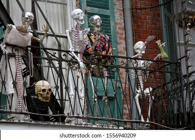 These skeletons are celebrating Halloween in New Orleans, Louisiana.  They are displaying beads and are on a balcony overlooking a street.  The beads are a symbol of Mardi Gras.
