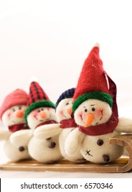These snowmen are bundled up to go sledding.  Copy space across top.  Selective Focus on lead snowman.