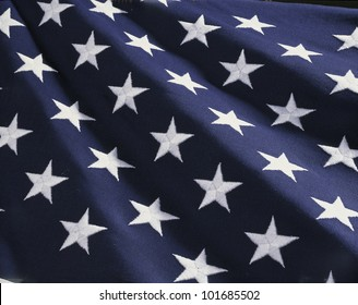 These are the stars of the American flag. They are against their blue field, climbing upward toward the corner of the image as if they were situated on small stairs that move up in levels..
