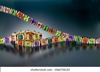 These two 14K yellow gold link tennis bracelet are channel set with a mix of round semiprecious colored gemstones including amethyst, garnet, peridot, citrine and iolite. Shown on a black background.