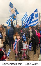 Thessaloniki / Greece - 01/21/2018 : a family is holding Greek flags celebrating  at the rally for the name Macedonia in Thessaloniki Greece