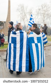 Thessaloniki / Greece - 01/21/2018 : Two unknown People celebrate at the Greek Rally for the Name Macedonia wearing the Greek Flag