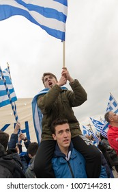 Thessaloniki / Greece - 01/21/2018 : two young men are celebrating at the Rally for the name of Macedonia in Thessaloniki Greece while waving a big Greek flag