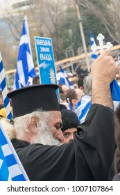 Thessaloniki / Greece - 01/21/2018 : unknown Greek Priest celebrate at the Greek Rally for the Name Macedonia holding a Greek flag with a cross on top