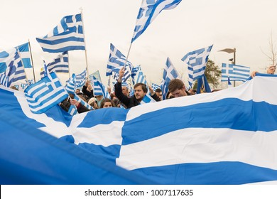 Thessaloniki / Greece - 01/21/2018 :  unknown Greek People celebrate at the Greek Rally for the Name Macedonia holding and waving big Greek Flags