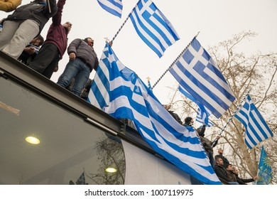 Thessaloniki / Greece - 01/21/2018 : unknown Greek People on top of a building celebrate at the Greek Rally for the Name Macedonia holdings signs and Greek Flags