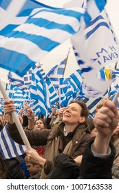 Thessaloniki / Greece - 01/21/2018 : Unknown Greek woman in the crowd is waving a big Greek Flag at the rally for the name Macedonia in Thessaloniki Greece