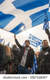Thessaloniki / Greece - 01/21/2018 : Unknown greek people are holding a huge Greek flag waving it on the air at the rally for the name Macedonia in Thessaloniki Greece