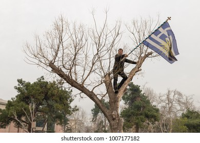 Thessaloniki / Greece - 01/21/2018 : Unknown Greek man climbed on a tree waving a huge Greek Flag at the rally for the name Macedonia in Thessaloniki Greece