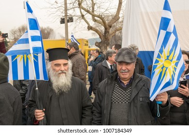 Thessaloniki / Greece - 01/21/2018 : Unknown Greek Priest and a man next to him are waving their Greek Flags at the rally for the name Macedonia in Thessaloniki Greece