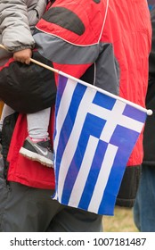 Thessaloniki / Greece - 01/21/2018 : unknown kid on his Dad's lap is holding a Greek flag at the rally for the name Macedonia in Thessaloniki Greece