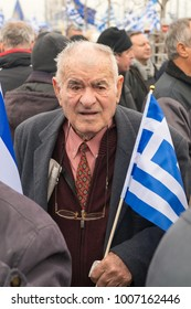 Thessaloniki / Greece - 01/21/2018 : Unknown old Greek man is holding a small Greek flag at the Rally for the name of Macedonia in Thessaloniki Greece