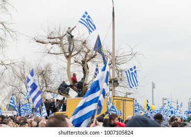 Thessaloniki / Greece - 01/21/2018 : unknown People celebrate at the Greek Rally for the Name Macedonia climbed on a tree and Holding Greek flags