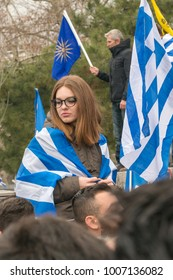 Thessaloniki / Greece - 01/21/2018 : a woman is on top of the shoulders of a man while she is wearing  the Greek Flag protesting at the Rally in Thessaloniki Greece for the name Macedonia