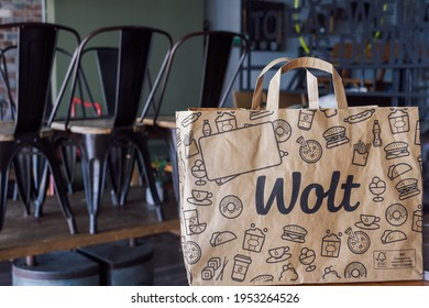 Thessaloniki, Greece - April 02 2021: Wolt food delivery bag with company logo, on restaurant. Finish company paper bag with handle, used by platform courier partners.