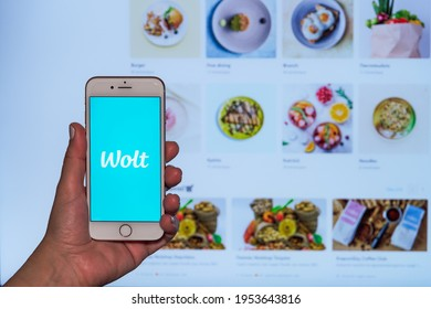 Thessaloniki, Greece - April 10 2021: Wolt food delivery order concept. Female hand holds before screen mobile phone with Finish company logo and web page with platform restaurant partners.