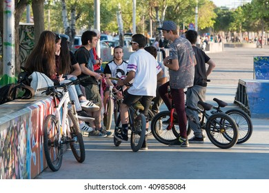 Thessaloniki, Greece - April 15, 2016: a group of kids enjoying their day at the park while talking on bikes and skateboards in Greece Thessaloniki