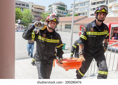 THESSALONIKI, GREECE- APRIL 24, 2013: Firemen carrying equipment and a stretcher into the building during an earthquake exercise at 6th primary school in Thessaloniki, Greece.