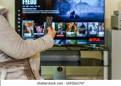 Thessaloniki, Greece - April 4 2020: Watching on TV Netflix streaming Service VoD content. Female in casual outfit with multimedia remote control in hand, views on large screen streaming provider page