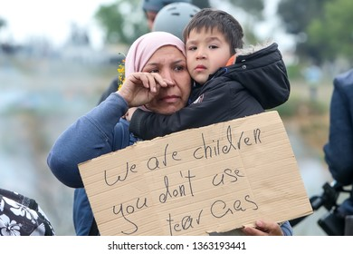 Thessaloniki, Greece - April 6, 2019:a refugee mother who is crying with her little son in her arms at a refugee camp in Diavata just realized she could not continue her journey from Greece to Europe.