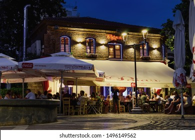 Thessaloniki, Greece - August 15 2019: Ladadika area with crowd & live bouzouki music on a tavern. Night view of an illuminated Greek taverna at a much visited pedestrian area with outdoors seating.