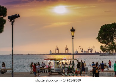 Thessaloniki, Greece - August 15 2019: Golden hour at waterfront with crowd. Thermaikos gulf seafront evening with street vendors & trailer selling cotton candy or popcorn before White Tower landmark.