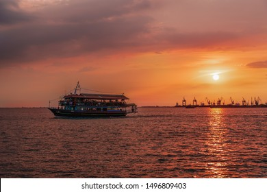 Thessaloniki, Greece - August 15 2019: Tourist ship sailing during a golden hour sunset.Unidentified crowd aboard a small ship at Thermaikos gulf during orange sunset, with port cranes background.