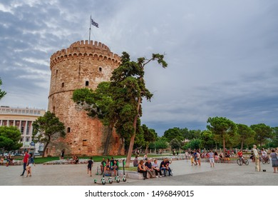 Thessaloniki, Greece - August 15 2019: Golden hour at the city landmark with crowd & Lime-S electric scooters. Evening view of unidentified crowd before White Tower with Greek flag waving on top.