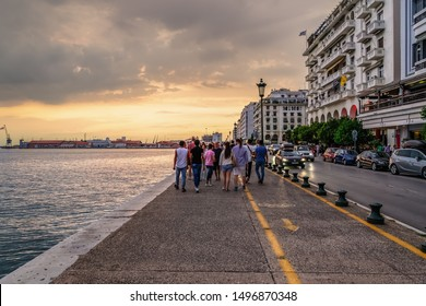 Thessaloniki, Greece - August 15 2019: Unidentified crowd at the historic waterfront. People walk along the promenade towards the city port during golden hour with passing cars at Nikis Avenue.