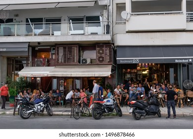 Thessaloniki, Greece - August 15 2019: People enjoy coffee at city center cafe bars. Unidentified crowd drinking frape or other beverage at outdoors seating bars in Nikis Avenue before the waterfront.