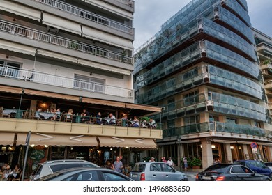 Thessaloniki, Greece - August 15 2019: People eating at a city tavern balcony. Unidentified crowd enjoying their Greek taverna food dinner in the center at Leoforos Nikis Avenue before the waterfront.