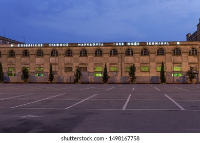Thessaloniki, Greece - August 15 2019: city port Makedonia cruise-passenger terminal facade. Illuminated evening view of commercial port 1910 neoclassical building with sign in Greek & English.