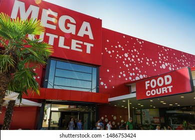 Thessaloniki, Greece - August 24 2019: MEGA Outlet shopping mall facade. Day view of discount shopping center entrance in Northern Greece at Pylaia area with crowd at the entrance next to food court.