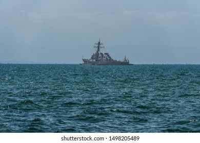 Thessaloniki, Greece - August 31 2019: USS MC Faul DDG-74 warship moored at open sea. United States Navy Arleigh Burke-class guided missile destroyer with Greek & USA flags waving outside port.